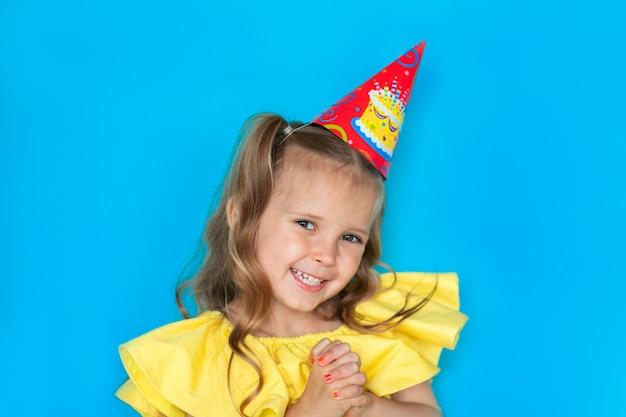 Portret van jong feestvarken in gele blouse en glb op een blauwe achtergrond met exemplaarruimte.