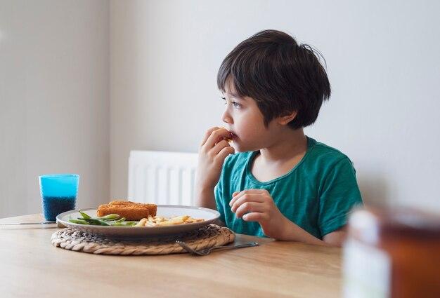 Portret van jong geitjejongen die eigengemaakte visvinger en frieten hebben voor zondagdiner thuis
