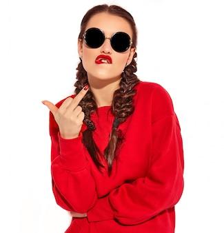 Portret van jong gelukkig het glimlachen vrouwenmodel met heldere make-up en kleurrijke lippen met twee geïsoleerde vlechten en zonnebril in de zomer rode kleren. fuck off teken tonen