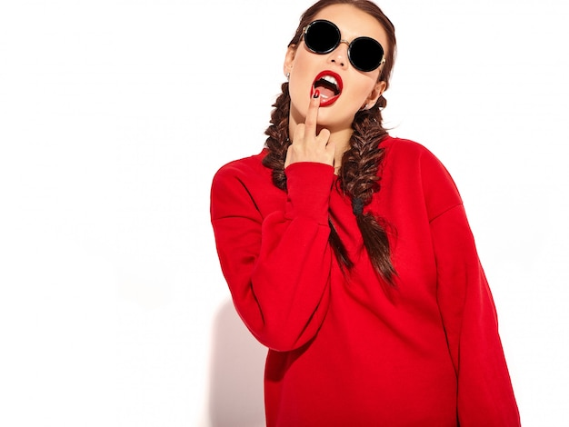 Portret van jong gelukkig het glimlachen vrouwenmodel met heldere make-up en kleurrijke lippen met twee geïsoleerde vlechten en zonnebril in de zomer rode kleren. middelvinger likken, rot op teken