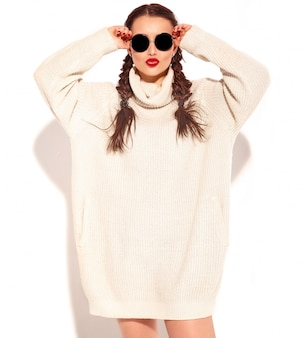Portret van jong gelukkig het glimlachen vrouwenmodel met heldere make-up en rode lippen met twee vlechten in geïsoleerde kleren van de de zomer de warme sweater.