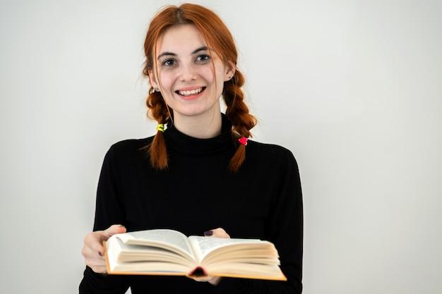 Portret van jong glimlachend studentenmeisje met een open boek in haar handen. lezen en onderwijs concept.