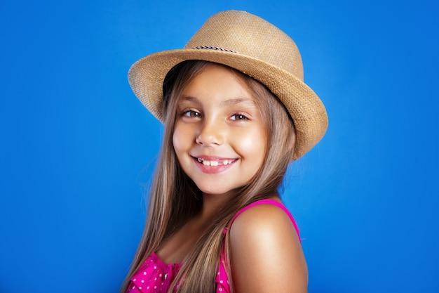 Portret van jong leuk meisje in roze kleding en hoed de zomervakantie en reisconcept