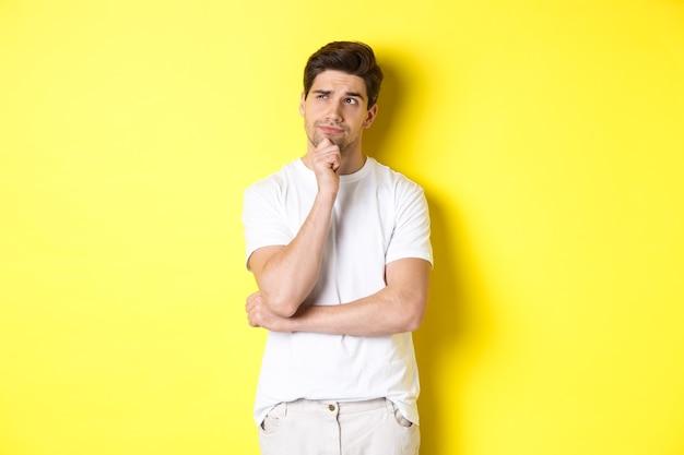 Portret van jong mannelijk model denken, de linkerbovenhoek bekijken en een keuze maken, staand dichtbij exemplaarruimte, gele achtergrond.