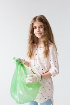 Portret van jong meisje die plastic zak recycleren