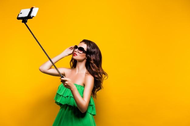 Portret van jong model in groene kleding en zonnebril die terwijl het maken van selfie stellen