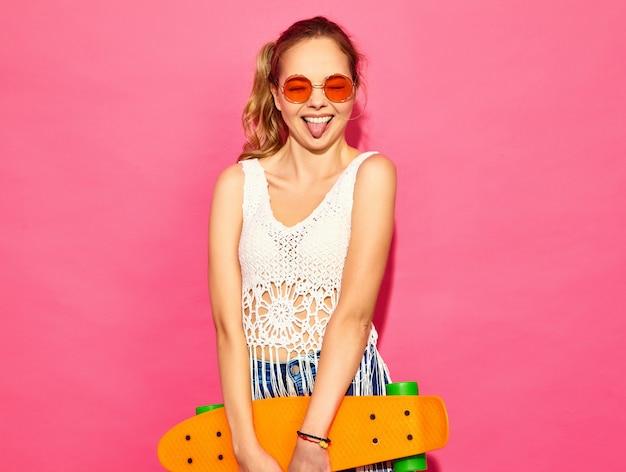 Portret van jong modieus het glimlachen blond vrouwenmodel met stuiverskateboard. vrouwen in de zomer witte jurk poseren in de buurt van roze muur en toont haar tong