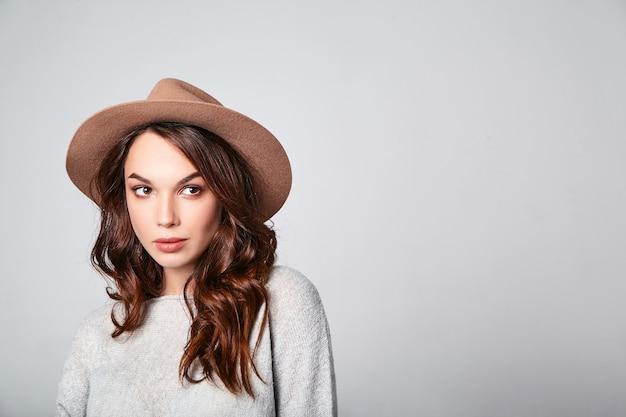 Portret van jong modieus het lachen model in grijze toevallige de zomerkleren in bruine hoed met natuurlijke make-up