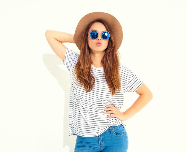 Portret van jong modieus lachend vrouwenmodel in toevallige de zomerkleren in bruine die hoed op witte muur wordt geïsoleerd