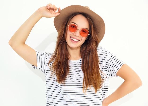 Portret van jong modieus lachend vrouwenmodel in toevallige de zomerkleren in bruine hoed met natuurlijke die make-up op witte muur wordt geïsoleerd.