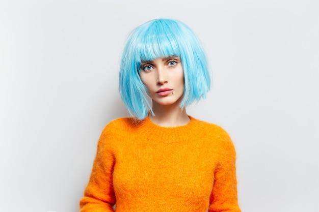 Portret van jong modieus meisje met blauw haar in oranje sweater tegen witte muur.