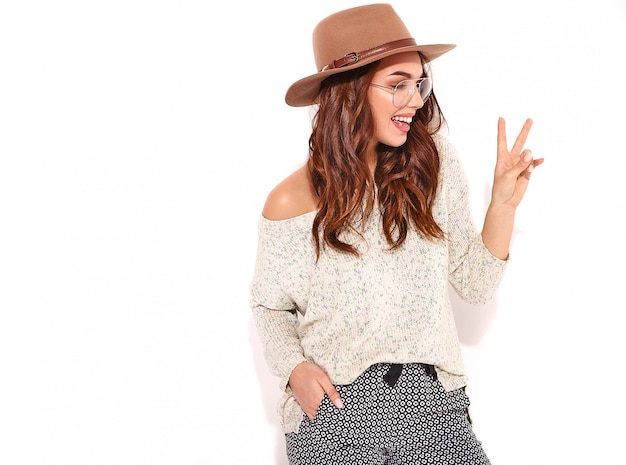 Portret van jong modieus meisjesmodel in toevallige de zomerkleren in bruine hoed met natuurlijke geïsoleerde make-up in glazen. en vredesteken tonen