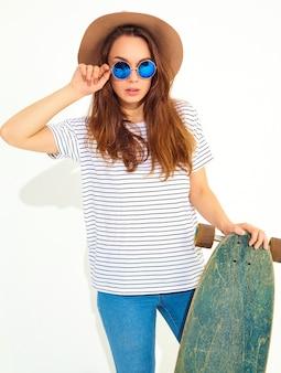 Portret van jong modieus vrouwenmodel in toevallige de zomerkleren in het bruine hoed stellen met longboardbureau. geïsoleerd op wit