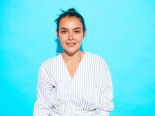 Portret van jong mooi glimlachend hipster meisje in trendy de zomerkleren. het sexy onbezorgde vrouw stellen dichtbij blauwe muur. positief model met plezier