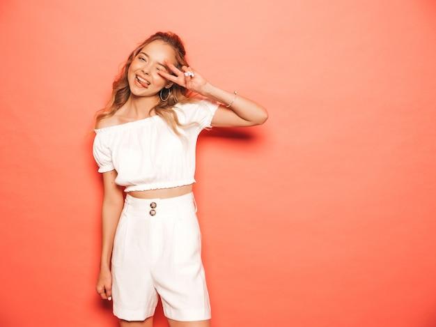 Portret van jong mooi glimlachend hipster meisje in trendy de zomerkleren. het sexy onbezorgde vrouw stellen dichtbij roze muur. positief model met plezier. toont teken en tong