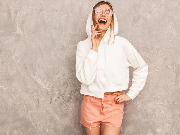 Portret van jong mooi glimlachend meisje in de kleren van de trendy de zomersport. het sexy onbezorgde vrouw stellen. positief model dat pret in zonnebril heeft