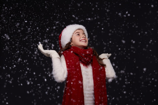 Portret van jong mooi glimlachend meisje in rode kerstmanhoed op een donkere achtergrond