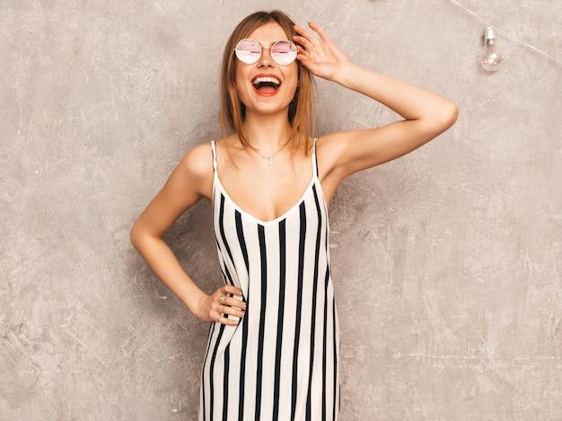 Portret van jong mooi glimlachend meisje in trendy de zomer gestreepte kleding. het sexy onbezorgde vrouw stellen. positief model dat pret in ronde zonnebril heeft