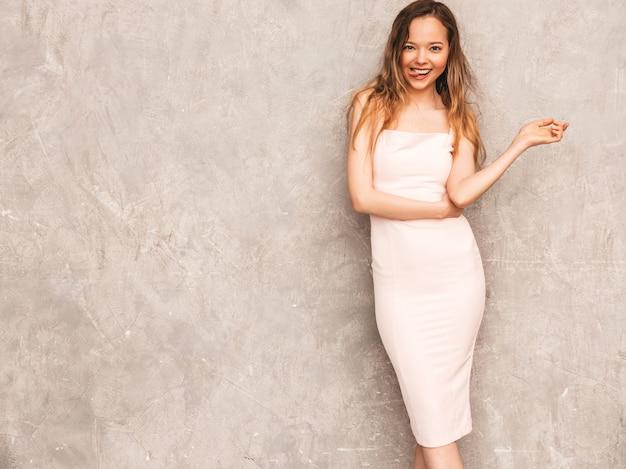 Portret van jong mooi glimlachend meisje in trendy de zomer lichtrose kleding. het sexy onbezorgde vrouw stellen. positief model dat pret heeft en haar tong toont