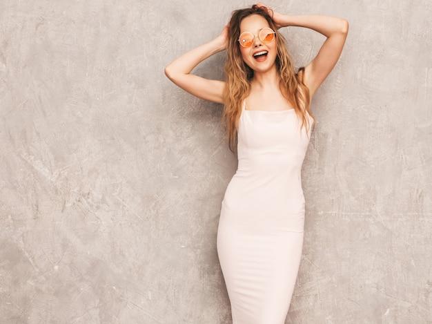 Portret van jong mooi glimlachend meisje in trendy de zomer lichtrose kleding. het sexy onbezorgde vrouw stellen. positief model dat pret in ronde zonnebril heeft