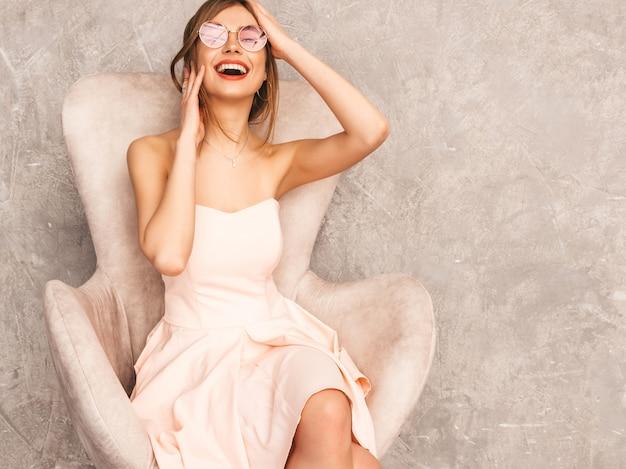 Portret van jong mooi glimlachend meisje in trendy de zomer lichtrose kleding. sexy zorgeloze vrouw zittend op beige stoel. poseren in luxe interieur