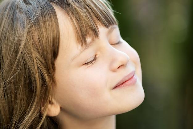 Portret van jong mooi kindmeisje dat met lang haar in openlucht van warme zonnige dag in de zomer geniet. schattige vrouwelijke jongen ontspannen op frisse lucht buiten.