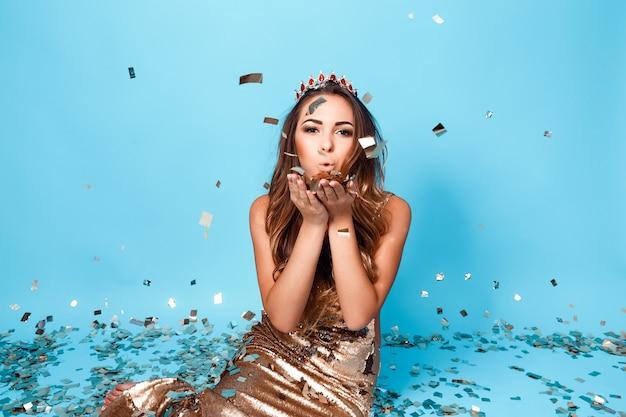 Portret van jong mooi meisje in gouden jurk en kroon poseren op blauwe achtergrond blaast confetti...