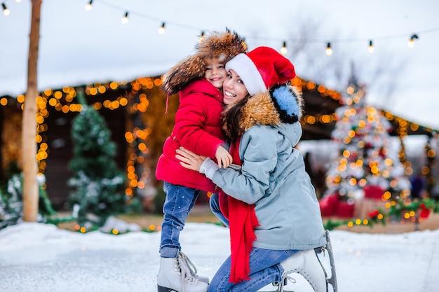 Portret van jong mooi meisje in traditionele russische bontmuts met oorkleppen en rode winterjas en witte schaatsen poseren met haar moeder op de ijsbaan tegen kerstmis achtergrond.