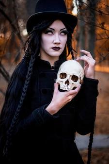 Portret van jong mooi meisje met donkere make-up op haar gezicht en skelet in handen