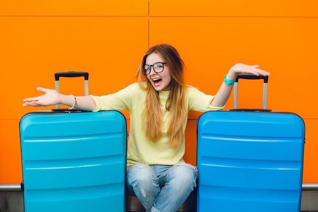 Portret van jong mooi meisje met lang haar in zwarte glazen, zittend op een oranje achtergrond tussen twee koffers. ze heeft lang haar en een gele trui met een spijkerbroek. ze lacht naar de camera.