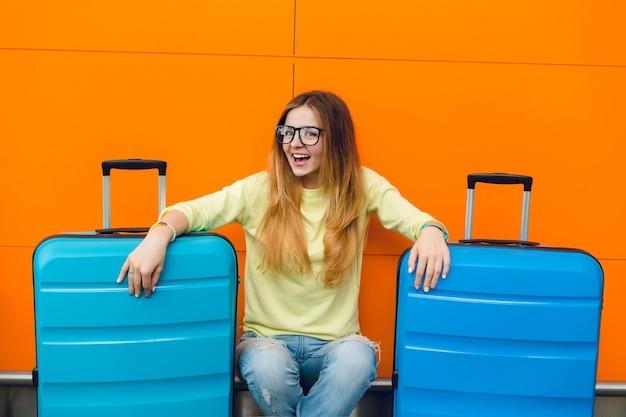 Portret van jong mooi meisje met lang haar, zittend op een oranje achtergrond tussen twee koffers. ze heeft lang haar en een gele trui, een spijkerbroek en een zwarte bril. ze lacht naar de camera.