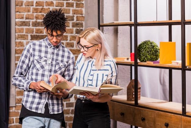 Portret van jong paar die tussen verschillende rassen het boek thuis lezen
