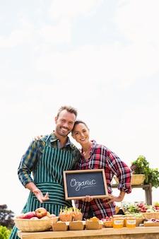 Portret van jong paar met bord dat organische groenten verkoopt