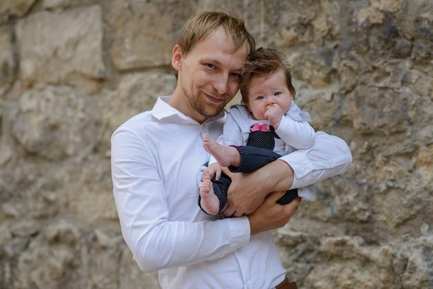 Portret van jong schreeuwend de babymeisje van de vaderholding over witte bakstenen muur