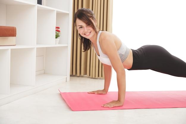Portret van jong sportief meisje glimlachen terwijl het doen van plankoefening