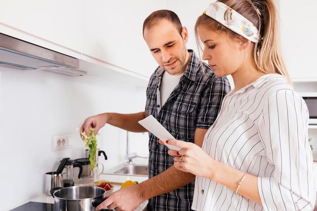 Portret van jong stel lezen recept boek tijdens het koken samen in de keuken