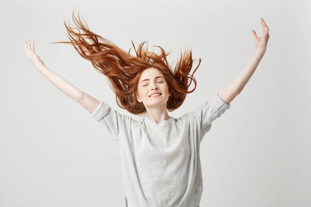 Portret van jong vrolijk mooi roodharigemeisje die met gesloten ogen glimlachen die haar schudden.