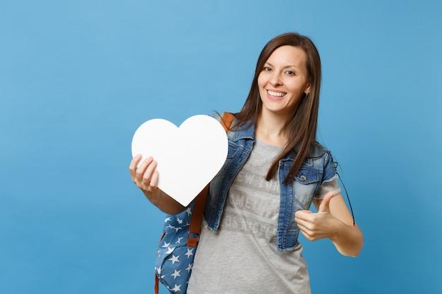 Portret van jonge aangename aantrekkelijke vrouw student met rugzak met wit hart met kopie ruimte duim opdagen geïsoleerd op blauwe achtergrond. onderwijs op de universiteit. kopieer ruimte voor advertentie.