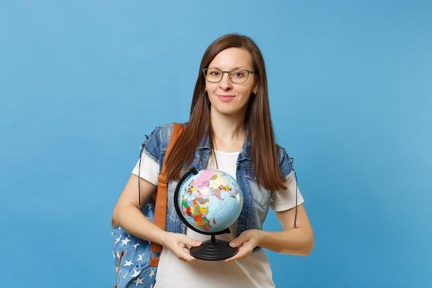 Portret van jonge aangename schattige vrouw student dragen van een bril met rugzak met wereldbol en leren geografie geïsoleerd op blauwe achtergrond. onderwijs in het concept van de middelbare schooluniversiteit.
