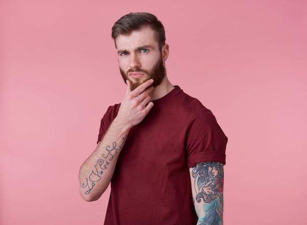 Portret van jonge aantrekkelijk denken getatoeëerde rode bebaarde man in rood t-shirt, kijkt naar de camera en raakt de kin, staat op roze achtergrond.