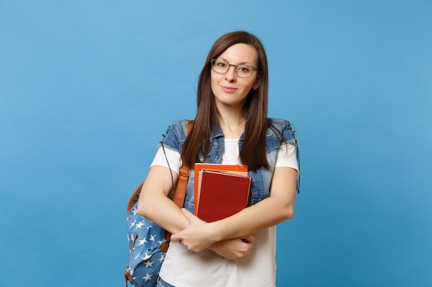 Portret van jonge aantrekkelijke aangename vrouw student bril met rugzak houden schoolboeken, klaar om te leren geïsoleerd op blauwe achtergrond. onderwijs in het concept van de middelbare schooluniversiteit.