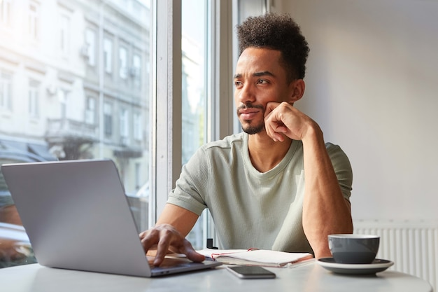 Portret van jonge aantrekkelijke afro-amerikaanse denkende jongen, zit aan een tafel in een café, werkt op een laptop en aromatische koffie drinkt en kijkt bedachtzaam naar het raam.