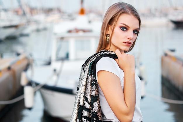Portret van jonge aantrekkelijke blondevrouw die in openlucht stellen