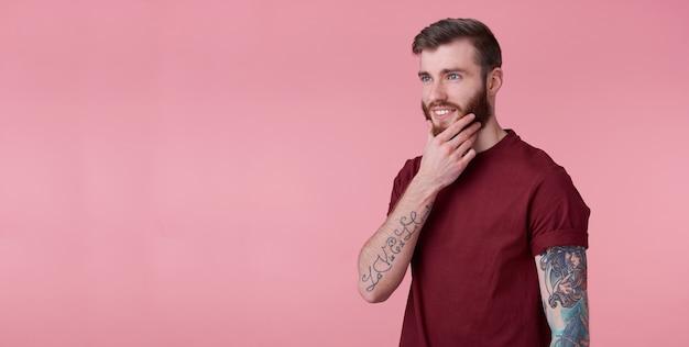 Portret van jonge aantrekkelijke denken getatoeëerde rode bebaarde man in rood t-shirt, kijkt weg en raakt de kin, glimlachend en raakt de kin, staat op roze achtergrond met copyspace.