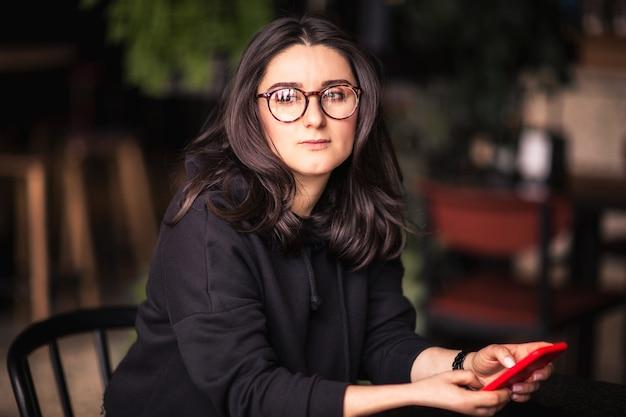 Portret van jonge aantrekkelijke donkerbruine vrouw die in glazen en zwarte hoodie rode telefoon houden
