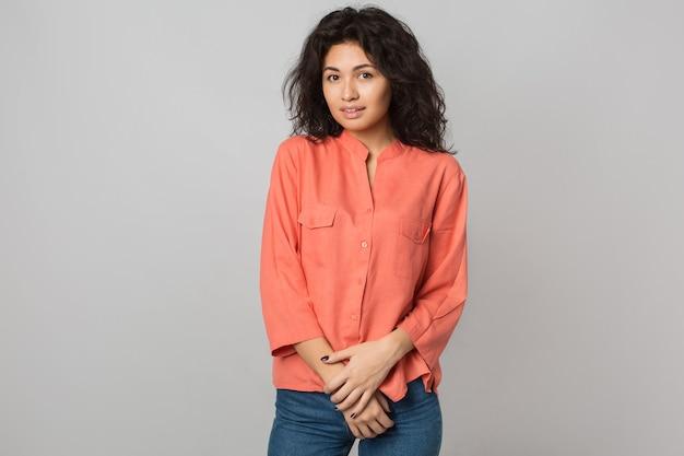 Portret van jonge aantrekkelijke donkerbruine vrouw in oranje overhemd