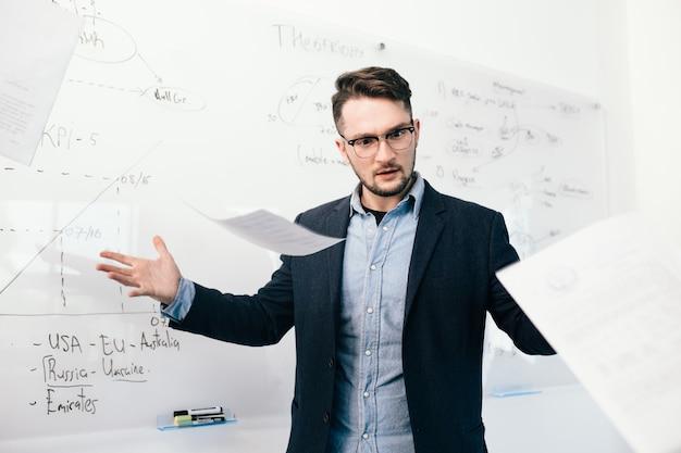 Portret van jonge aantrekkelijke donkerharige man in glazen documenten gooien in kantoor. hij staat bij een wit bureau met planning. hij draagt een blauw shirt met een zwarte jas.