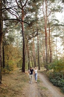 Portret van jonge aantrekkelijke gezin met zoontje, poseren in mooie herfst dennenbos op zonnige dag. knappe man en zijn mooie brunette vrouw