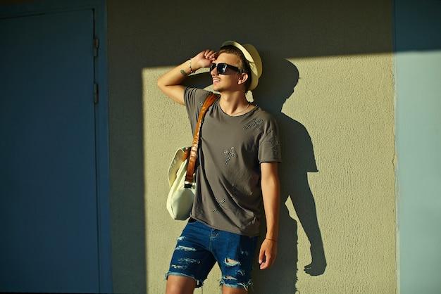 Portret van jonge aantrekkelijke glimlachende moderne stijlvolle man in casual doek in hoed met zonnebril staande in de buurt van muur