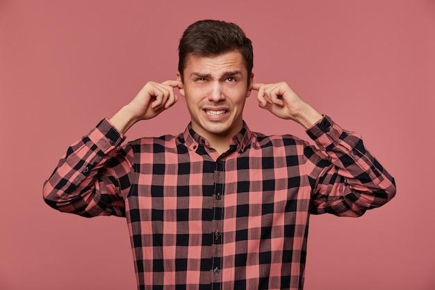 Portret van jonge aantrekkelijke kerel in geruit overhemd, kijkt naar de camera, staat op roze achtergrond en bedekt oren van hard geluid.